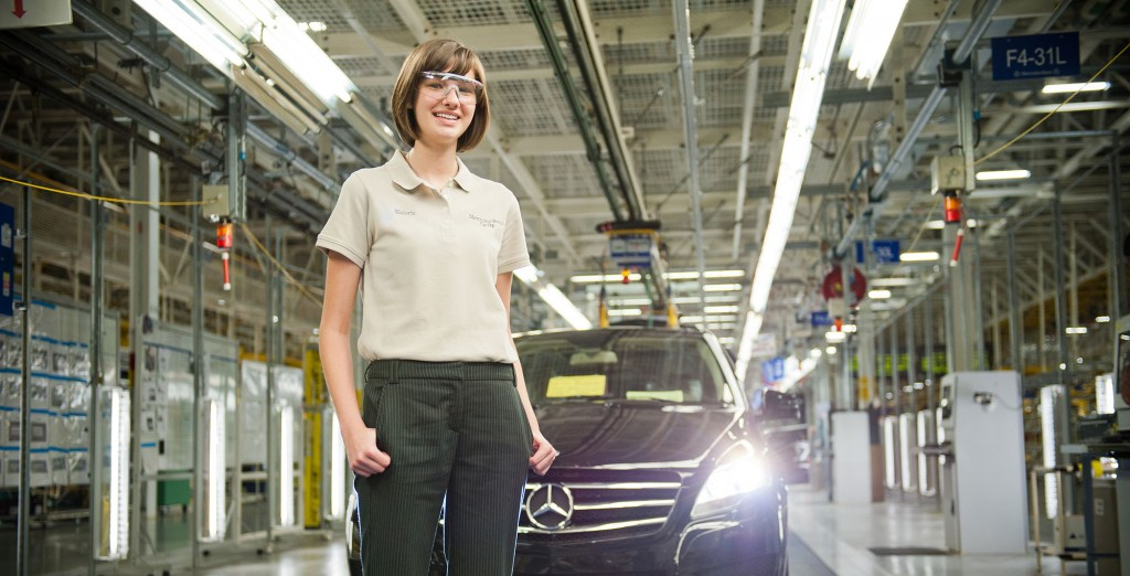 Female student standing in front o fa mercedes in a car factory